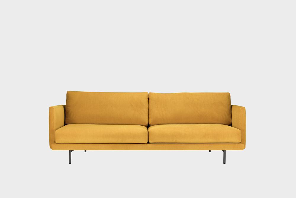 Kolmenistuttava Lazy-sohva okran värisellä Soft-kankaalla ja metallijalalla.