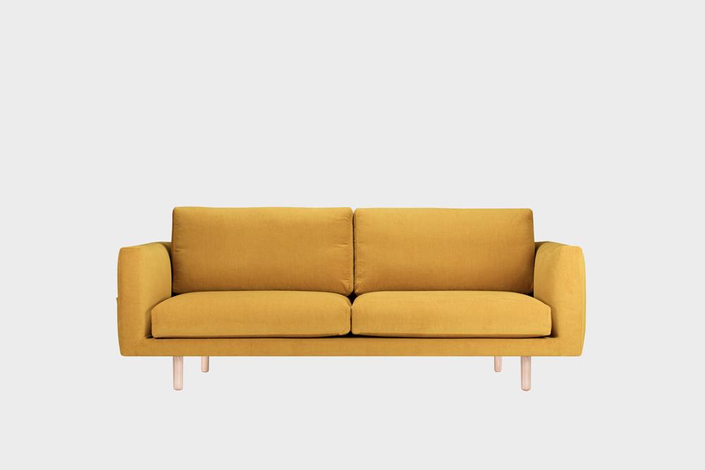Cosy Pocket -sohva okran värisellä Soft-kankaalla ja koivujalalla.