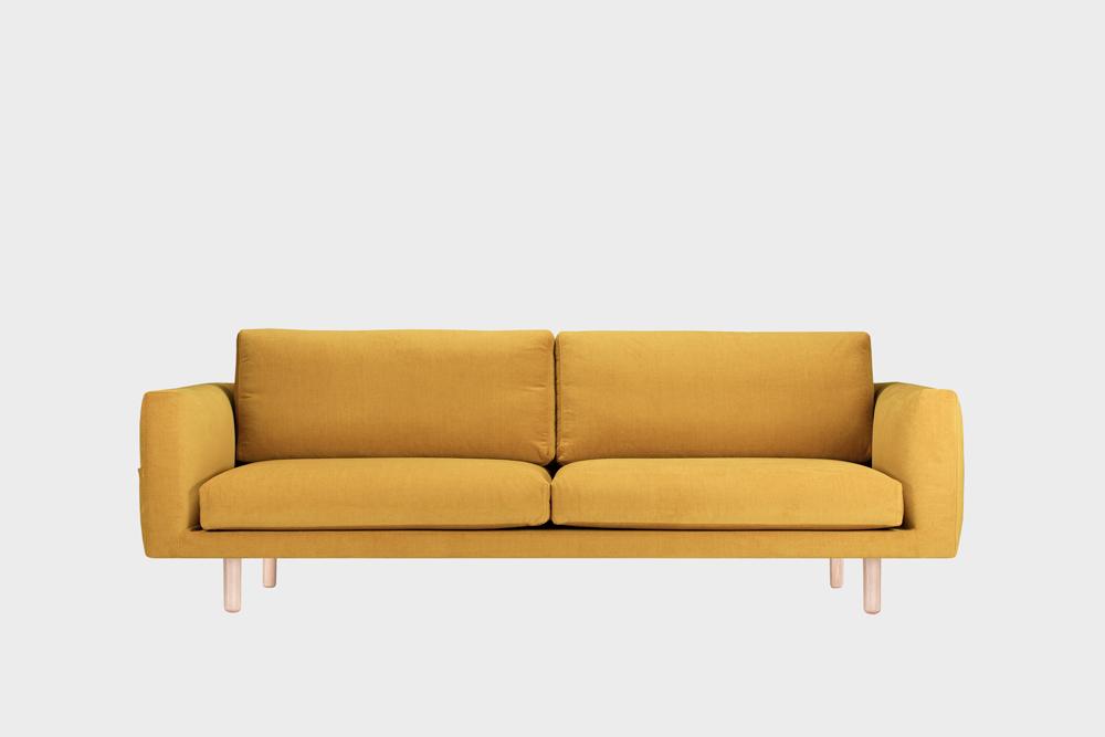 Iso Cosy Pocket -sohva okran värisellä Soft-kankaalla ja koivujalalla.