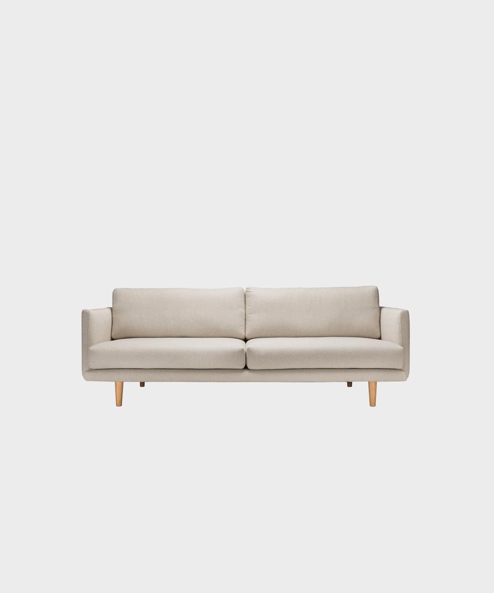 Kolmenistuttava Lazy-sohva hiekan värisellä Florist-kankaalla ja tammijalalla.