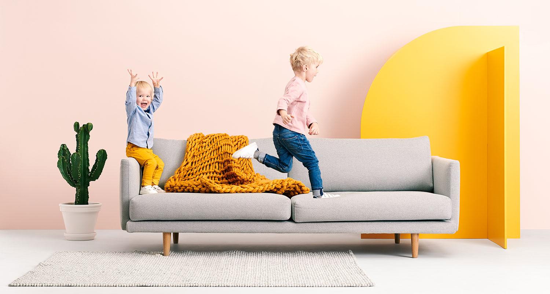 Lapset leikkivät vaaleanharmaalla Lazy-sohvalla.