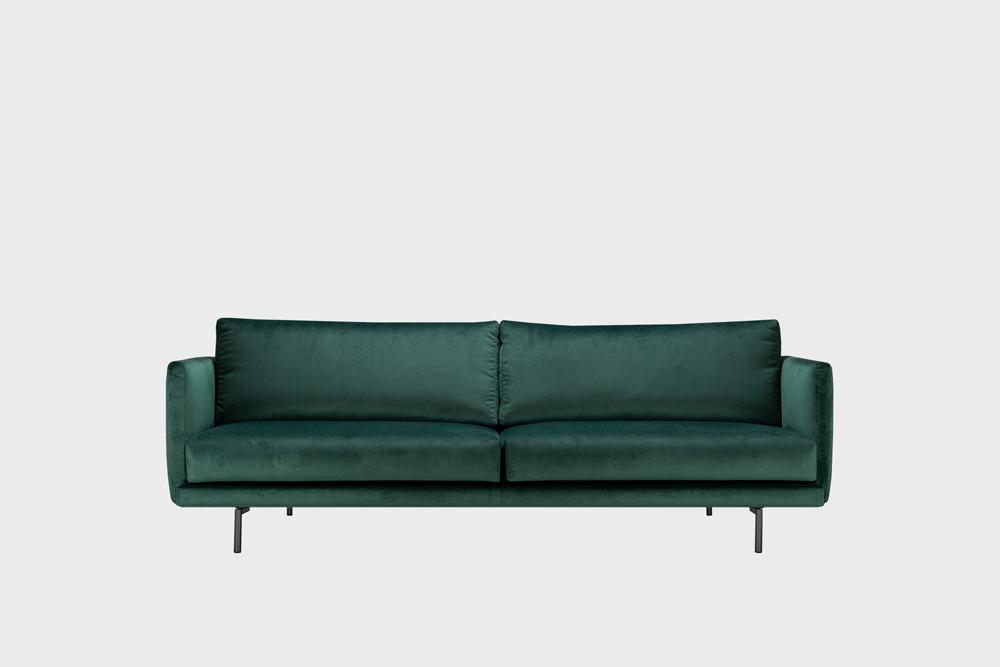 Lazy Velvet -sohva tummaanvihreällä Musone-kankaalla ja metallijalalla.