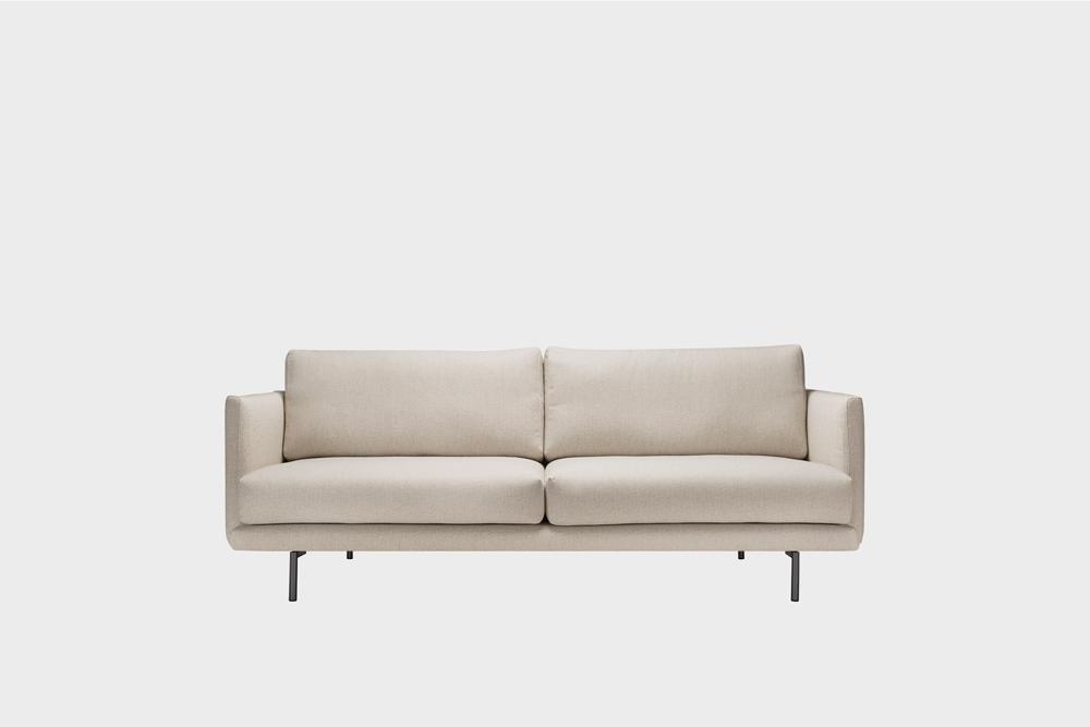 Pieni Lazy-sohva hiekan värisellä Florist-kankaalla ja metallijalalla.
