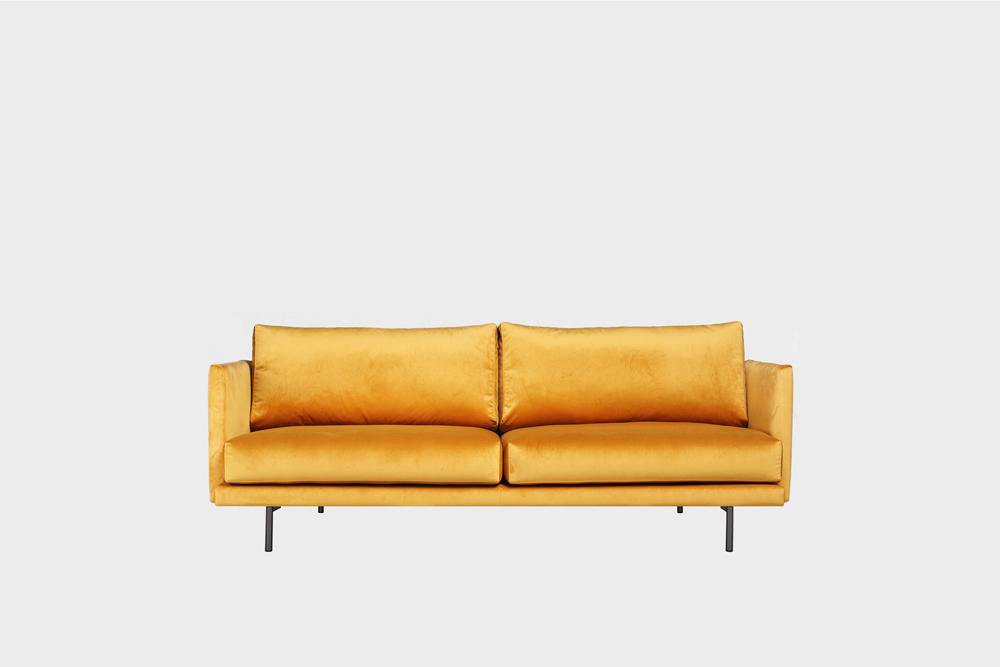 Pieni Lazy-sohva okran värisellä Musone-kankaalla ja metallijalalla.