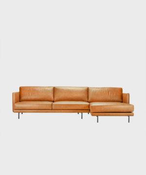 Hakola Lazy Leather -divaani konjakin värisellä Fine Leather -nahalla ja mustilla metallijaloilla.