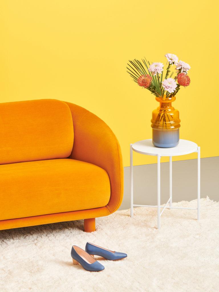 Hakola 2:n istuttava Bobo Velvet -sohva oranssilla Velvet-kankaalla ja round-sohvapöytä valkoisena.