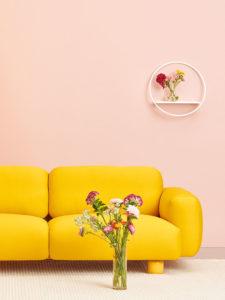Hakola Jumbo Wool 3:n istuttava -sohva okran värisellä Planum-kankaalla ja valkoinen Lempi-hylly.