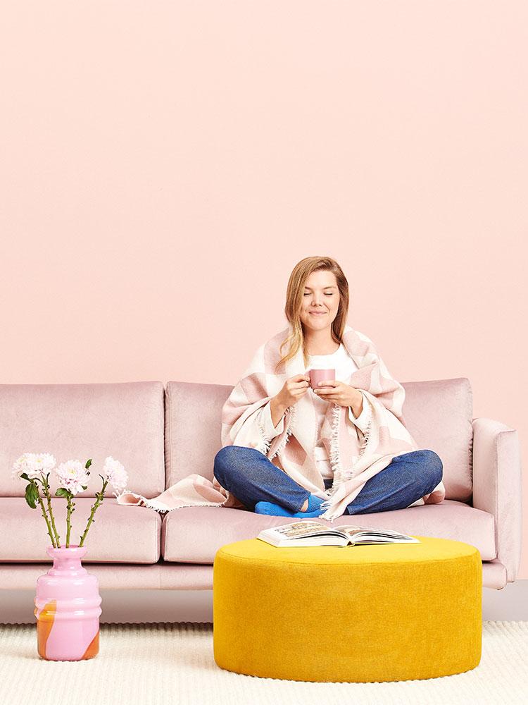 Hakola Lazy 3:n istuttava sohva vaaleanpunaisella Musone-kankaalla, Moon-rahi okran värisellä soft-kankaalla ja Laine-villahuopa vaaleanpunaisena.