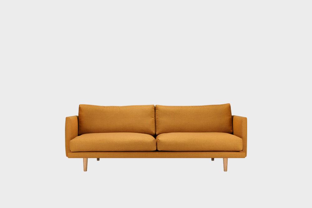 Hakola Lazy Wool pieni -sohva okran värisellä Canvas-kankaalla ja tammijaloilla.