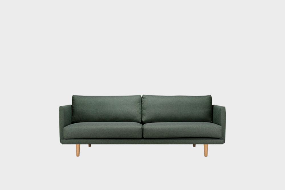 Hakola Lazy Wool pieni -sohva sammaleenvihreällä Canvas-kankaalla ja tammijaloilla.