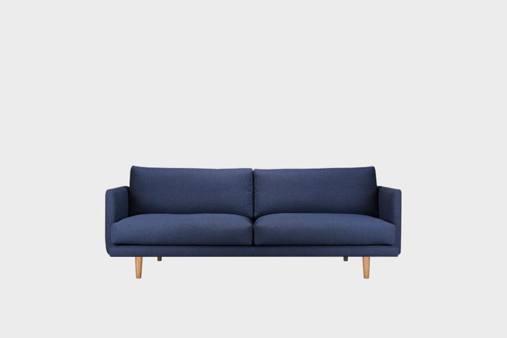 Hakola Lazy Wool pieni -sohva tummansinisellä Canvas-kankaalla ja tammijaloilla.