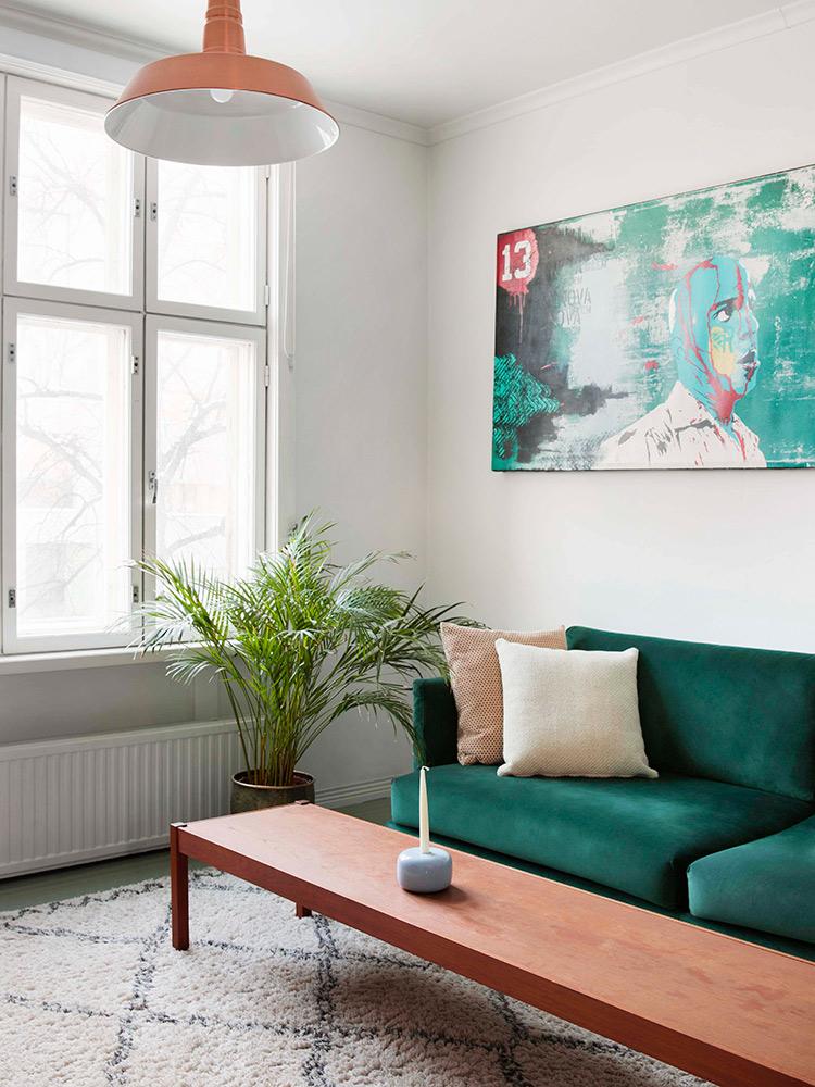Hakola Friends: Lazy Velvet 3:n istuttava sohva tummanvihreällä Musone-kankaalla, Sulo-kynttilänjalka vaaleansinisenä ja Puno-sisustustyyny luonnonvalkoisena.