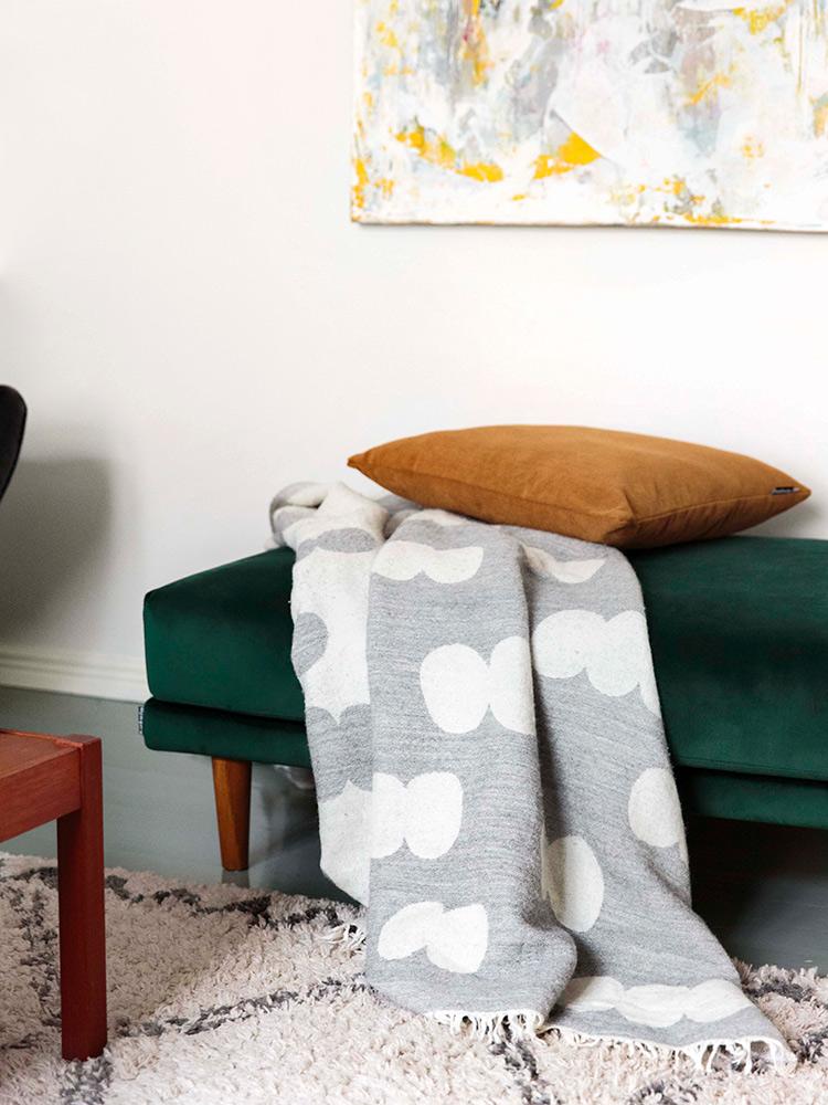 Hakola Friends: Lazy Velvet iso -rahi tummanvihreällä Musone-kankaalla ja Pampu-villahuopa harmaana Impun kotona