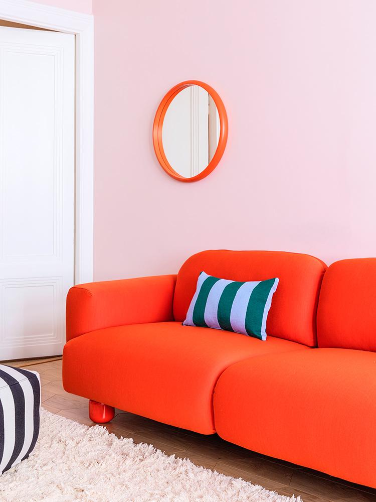 Hakola Bonbon pyöreä -peili oranssi, Jumbo Wool sohva punaisella Planum-kankaalla ja Jokiraita-sisustustyyny sinivihreänä